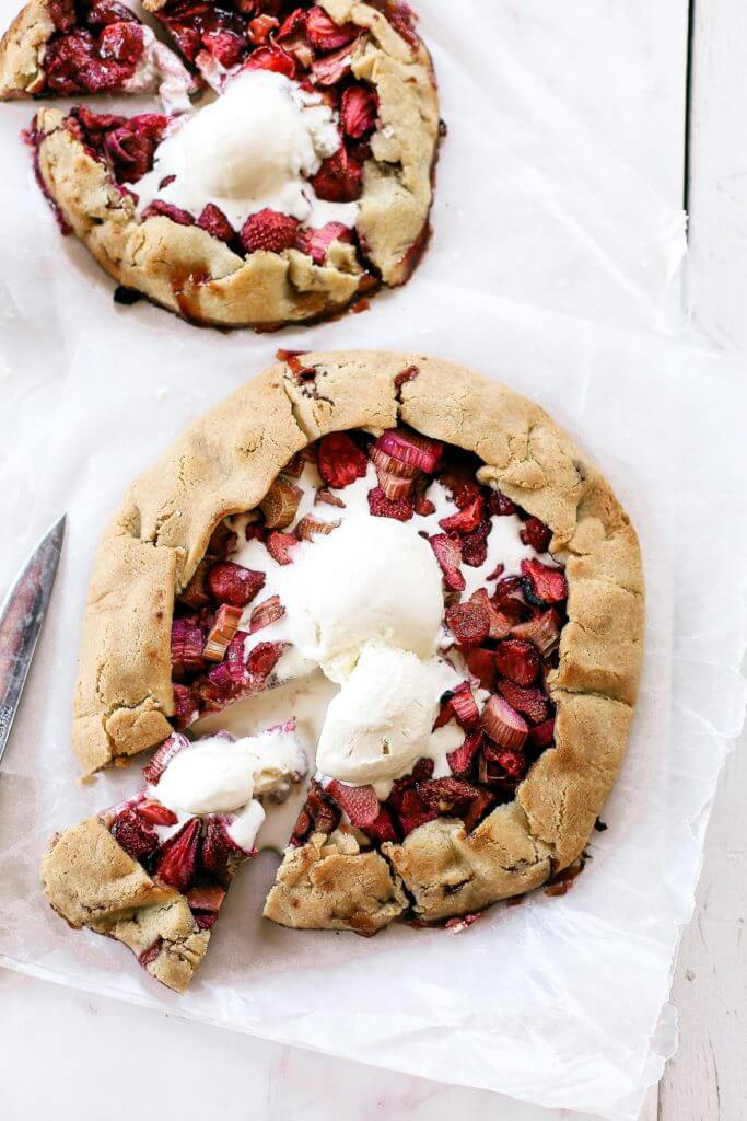 "Incredibly easy grain free & paleo strawberry rhubarb galette. A healthy and simple summer treat made with whole food ingredients. Naturally gluten free and dairy free. Sweetened without refined sugar. That sugary gooey fruit filling is to die for! Especially paired with a light and ""buttery"" almond flour crust. Gluten free galette. Paleo fruit galette. best paleo strawberry galette. easy healthy galette recipe. paleo galette recipe. easy gluten free summer desserts. grain free pie crust. grain free strawberry rhubarb galette."