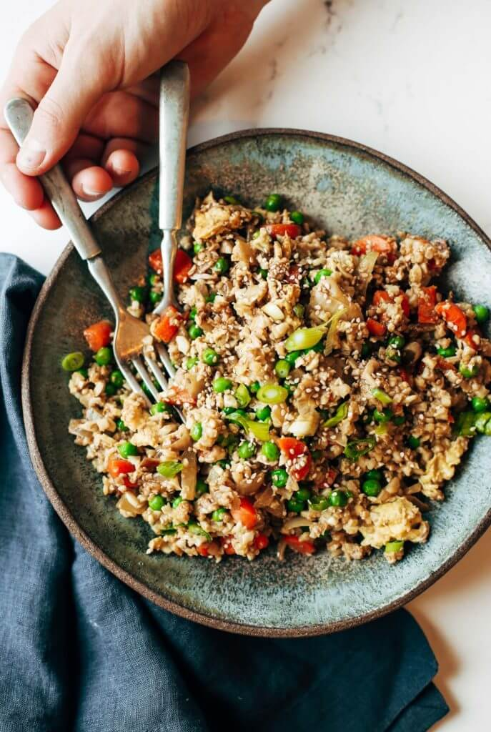 "Easy 10 minute fried cauliflower rice- whole30 and paleo! Make ahead and freeze! A healthy and fun family dinner. Topped with a homemade date sweetened gooey silky smooth ""soy sauce"", green onions, and sesame seeds. whole30 meal plan. Easy whole30 dinner recipes. Easy whole30 dinner recipes. Whole30 recipes. Whole30 lunch. Whole30 meal planning. Whole30 meal prep. Healthy paleo meals. Healthy Whole30 recipes. Easy Whole30 recipes. Easy whole30 dinner recipes. Best whole30 dinner recipes. Best cauliflower fried rice recipe. Easy fried rice. Best fried rice. Healthy paleo dinner recipe. Easy paleo meal ideas."