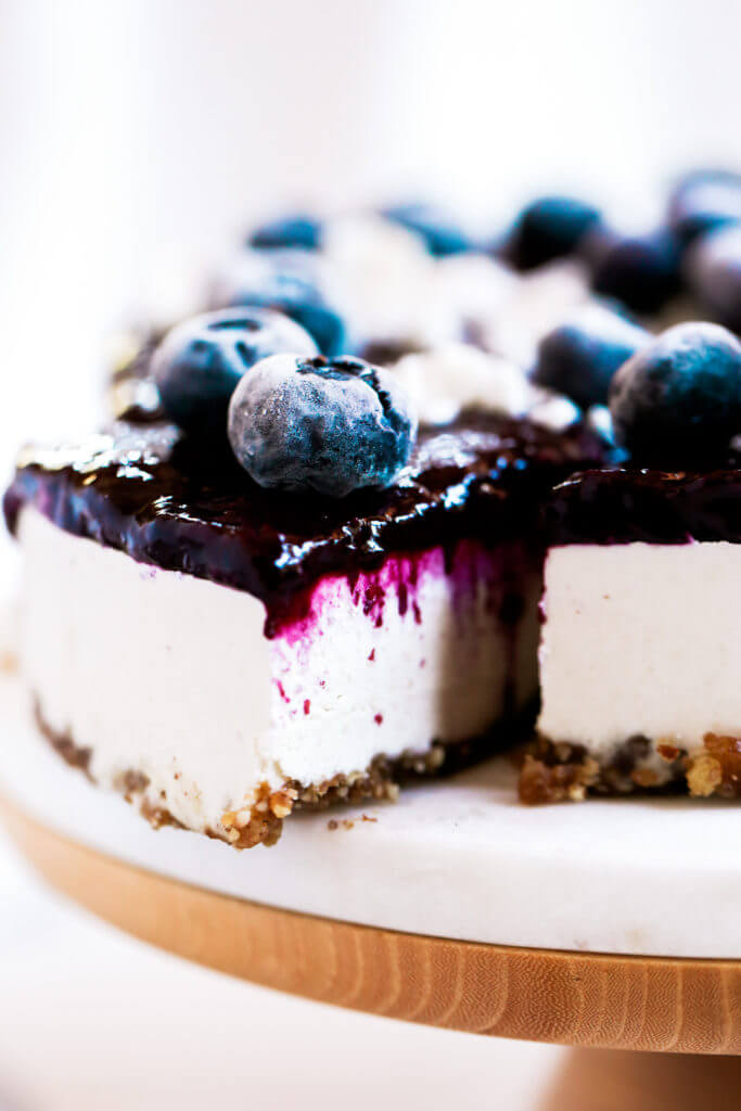 Can you believe it's real!? Healthy paleo yogurt cheesecake recipe. Filled with a tangy and sweet creamy yogurt filling and topped off with fresh blueberry compote. Vegan, gluten free, and dairy free! Incredibly creamy and satisfying! Raw paleo cheesecake recipe. No bake cashew cheesecake. Best gluten free vegan cheesecake. Raw paleo cheesecake recipe. No bake cheesecake recipe. Paleo cream cheese. Best paleo dessert recipes. easy cashew cheesecake. Blueberry cake recipes. best paleo blueberry cake. cherry photography. cake photography.