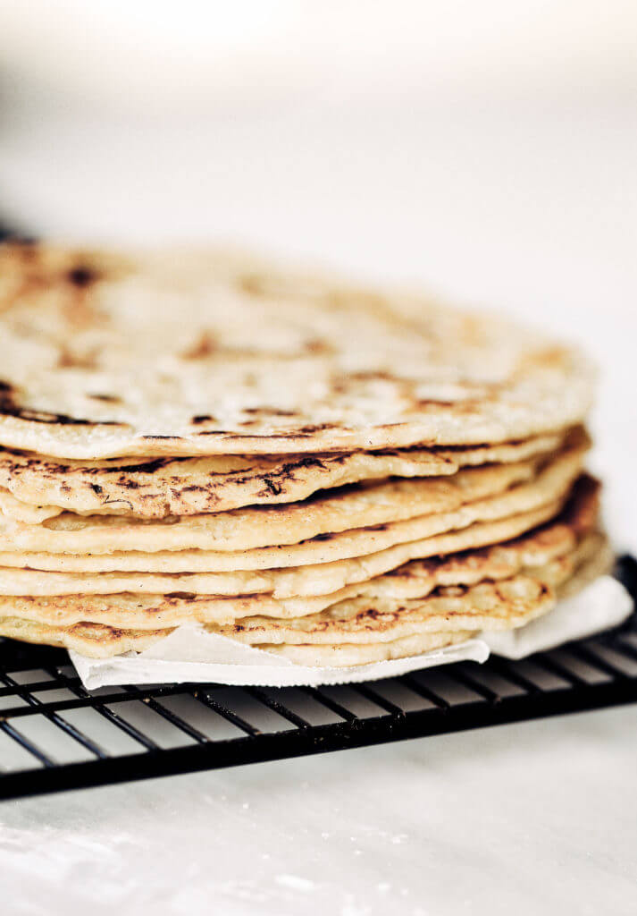 Thin soft shell paleo tortillas made in five minutes! No rolling out required. Make these soft gluten free blender by blending almond flour, tapioca flour, avocado oil, and coconut milk in a blender. Pour batter onto a skillet and out comes the most beautiful and tasty grain free tortillas, perfect for taco night or a breakfast burrito! The easiest, most versatile, fool proof, and delicious paleo flour tortillas! Easy gluten free tortilla recipe. best gluten free tortilla recipe. Best paleo tortilla recipe. Easy paleo tortillas. Healthy tortillas.