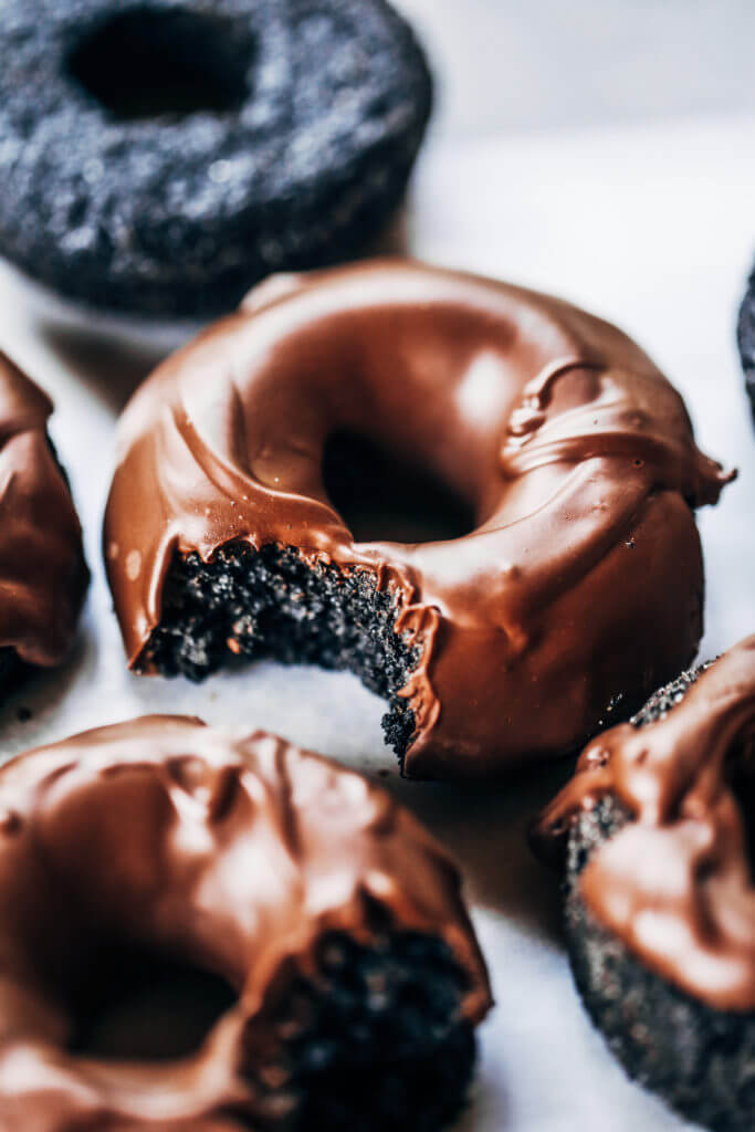 Healthy paleo chocolate glazed donuts made with sweet potato instead of flour! Easy baked donut recipe perfect for celebrations! Baked gluten free chocolate donuts. #paleo #donuts #dessert #chocolate