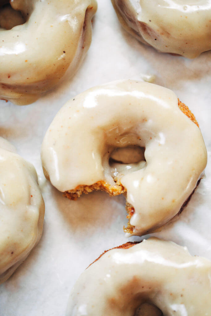 Ready for this fall favorite? Paleo pumpkin pie glazed donuts- made with white sweet potato instead of flour... It truly doesn't get any better! The texture is soft and fluffy, the flavor is pumpkin pie in real life, and the glaze is EVERYTHING. Easy gluten free donut recipe. Best paleo baked donuts! #paleo #donuts #pumpkinspice #baking