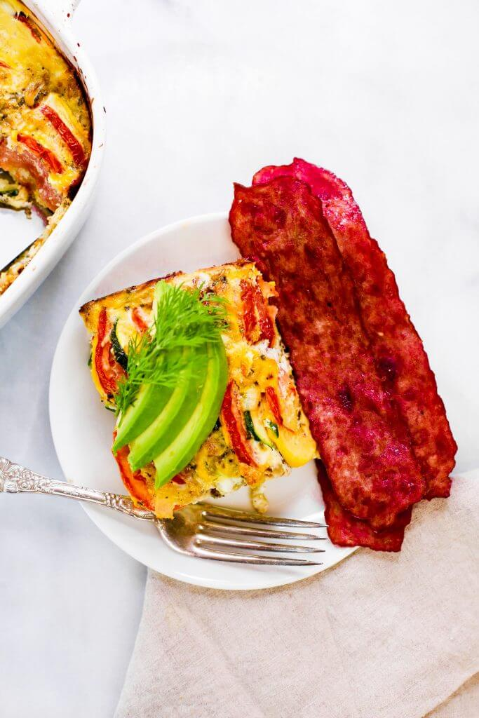 Easy whole30 egg and zucchini breakfast bake with tomatoes, yellow squash, herbs, and zucchini. This paleo breakfast is perfect for meal prep at the beginning of the week and paired with one of my homemade sweet potato tortillas! #paleo #whole30 #bacon