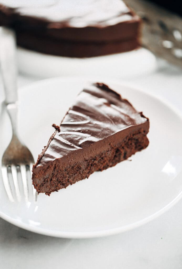 Flourless chocolate cake recipe. Paleo and dairy free fudgey chocolate cake with a thick layer of chocolate frosting. This easy chocolate cake will win hearts over and make you go back for seconds. #cake #chocolate #desserts #baking #paleo