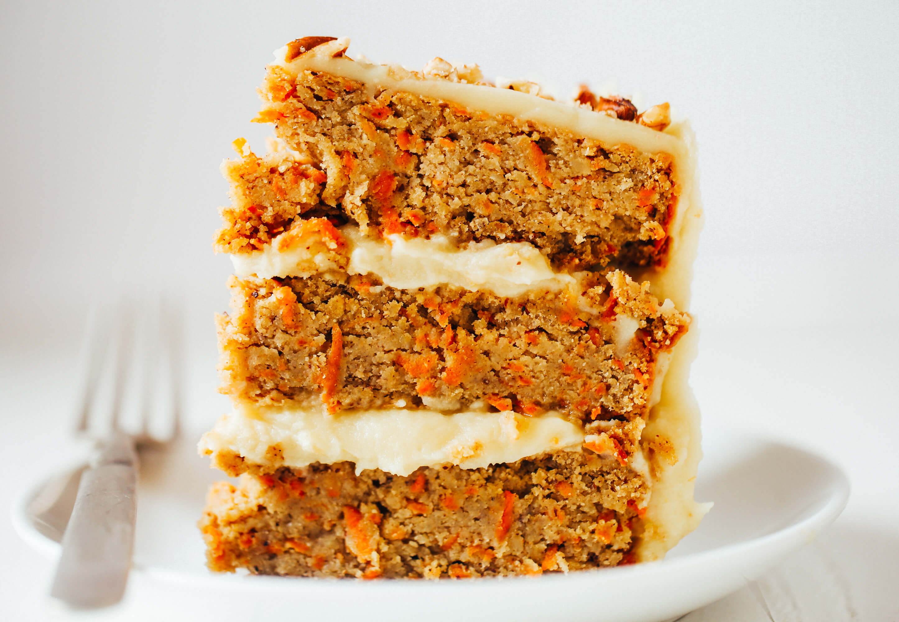 Paleo carrot cake made with sweet potatoes. Topped with creamy lemon frosting made from white sweet potatoes. A healthy carrot cake recipe that is gluten free and dairy free. Moist and flavorful carrot cake perfect for spring! #cake #baking #paleo #recipes